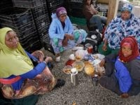 June, 2014: Somali refugees, working as farm hands, share lunch under a shelter as a steady rain falls at Red Fire Farm in Massachusetts.