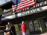 "FILE - In this Dec. 25, 2014, file photo, a visitor takes a selfie with his friend in front of the Cinefamily at Silent Movie Theater in Los Angeles, prior to attending the movie ""The Interview."" The independent movie theater Cinefamily, which had numerous celebrity supporters, said Tuesday, Nov. 14, …"