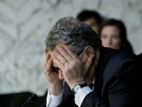 Sen. Al Franken with head down and face covered