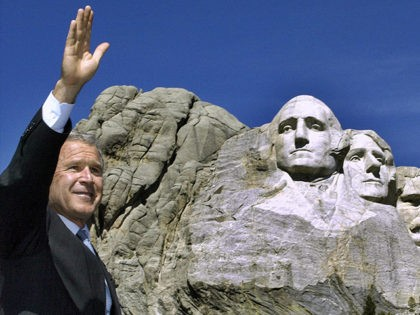 KEYSTONE, UNITED STATES: US President George W. Bush waves to the crowd at the foot of Mt. Rushmore 15 August 2002 in Keystone, South Dakota. Sculptor Gutzon Borglum started work on Mt. Rushmore 10 Aug 1927 and continued for 14 years, but only 6.5 years were actually spent sculpting due …
