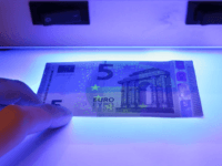 MAINZ, GERMANY - APRIL 26: The new 5 Euro note is displayed under a UV light at the German Bundesbank Counterfeit Money Analysis Lab during a demonstration for the media on April 26, 2013 in Mainz, Germany. The center is Germany's main facility for analysing potentially counterfeit money and also …