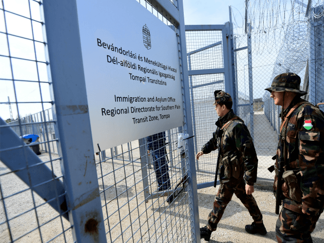 Hungarian soldiers enter the transit zone of Tompa border station on April 6, 2017 as the Hungarian Interior Minister Sandor Pinter (not pictured) presents the camp to the media. The migrant transit complex on the Hungarian side of the border has been expanded to become one of two new detention …