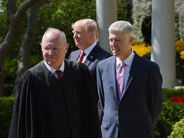 (L-R) Justice Anthony Kennedy, US President Donald Trump, and Neil Gorsuch take part in Gorsuch's swearing-in ceremony as an associate justice of the US Supreme Court in the Rose Garden of the White House on April 10, 2017 in Washington, DC. / AFP PHOTO / MANDEL NGAN (Photo credit should …