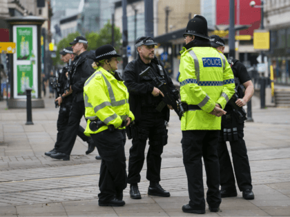 Armed police stand guard near the start of the Great Manchester Run in Manchester on May 28, 2017. Britain police have released CCTV footage of Manchester bomber Salman Abedi on the night of the attack as thousands defied the terror threat to take part in the Great Manchester Run on …