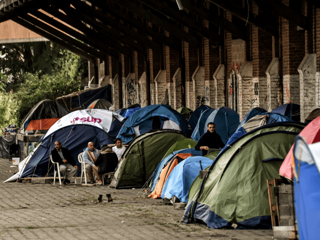 Men sit outside tents on October 6, 2017 in Lille, northern France at a migrants and refugees makeshift camp in the former station of St Sauveur. / AFP PHOTO / PHILIPPE HUGUEN (Photo credit should read PHILIPPE HUGUEN/AFP/Getty Images)
