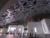 A general view shows people walking under the dome at the Louvre Abu Dhabi Museum that was designed by French architect Jean Nouvel during its inauguration on November 8, 2017 on Saadiyat island in the Emirati capital.