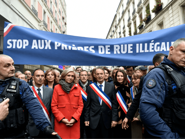 Clichy's mayor Remi Muzeau (C), and President of the Regional Council of the Ile-de-France region Valerie Pecresse (L), lead a demonstration as they walk under a banner reading 'Stop to illegal prayers in the streets' during a protest against muslim streets prayers, on November 10, 2017, in Clichy, near Paris. …