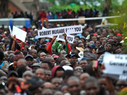 People hold anti-Mugabe placards during a demonstration demanding the resignation of Zimbabwe's president on November 18, 2017 in Harare. Zimbabwe was set for more political turmoil November 18 with protests planned as veterans of the independence war, activists and ruling party leaders called publicly for Zimbabwe's President to be forced …