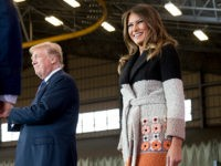 President Donald Trump, center, and first lady Melania Trump, right, take the stage at a hanger rally at Yokota Air Base, Sunday, Nov. 5, 2017, in Fussa, on the outskirts of Tokyo, Japan. (AP Photo/Andrew Harnik)