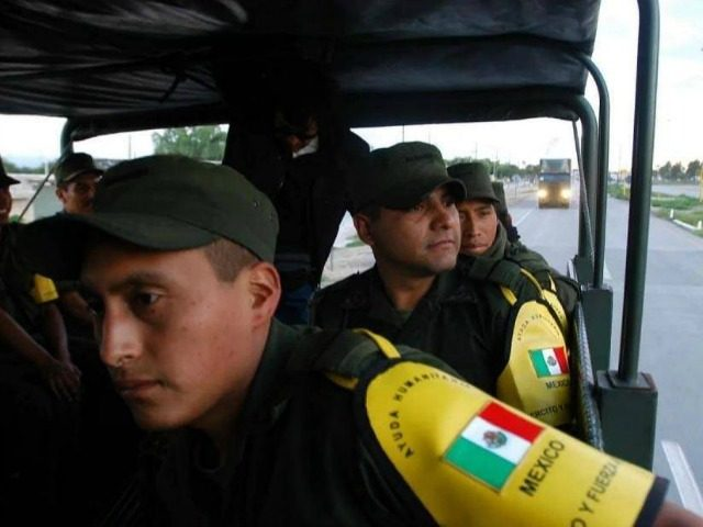 Mexican soldiers en route to the US border on 6 September 2005. The convoy was carrying water-treatment plants, mobile kitchens and supplies for the victims of Hurricane