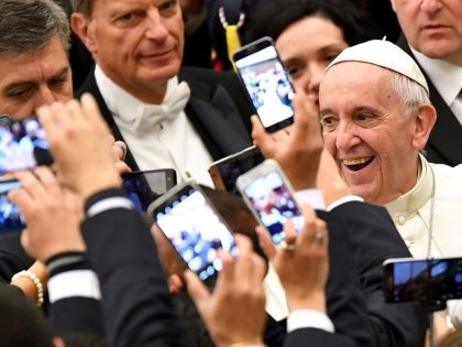 TOPSHOT - Pope Francis (R) arrives to lead his weekly general audience at Paul VI hall on December 21, 2016 at the Vatican as people take pictures of him with their cell-phone. / AFP / Alberto PIZZOLI (Photo credit should read ALBERTO PIZZOLI/AFP/Getty Images)