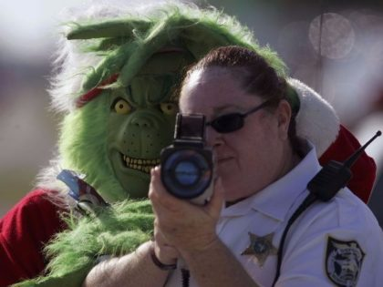 The Grinch stands behind a police officer using a laser speed detector