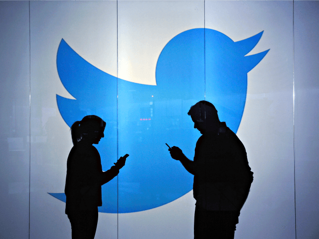 People are seen as silhouettes as they check mobile devices whilst standing against an illuminated wall bearing Twitter Inc.'s logo in this arranged photograph in London, U.K., on Tuesday, Jan. 5, 2016. Twitter Inc. may be preparing to raise its character limit for tweets to the thousands from the current …