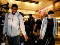 UCLA basketball players Cody Riley, left, LiAngelo Ball, right, and Jalen Hill, background center, are surrounded by the media as they leave the Los Angeles International Airport on Tuesday, Nov. 14, 2017, in Los Angeles. The three UCLA basketball players detained in China on suspicion of shoplifting returned home, where …