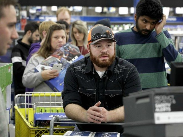 People line up to check out as they shop a Black Friday sale at a Best Buy store on Thanksgiving Day, Thursday, Nov. 23, 2017, in Overland Park, Kan. Shoppers are hitting the stores on Thanksgiving as retailers under pressure look for ways to poach shoppers from their rivals. (AP …