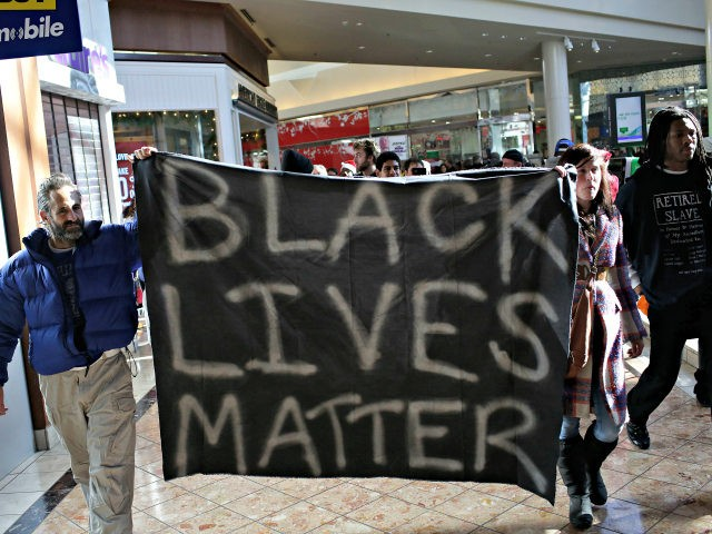 Demonstrators protesting the shooting death of Michael Brown hold a banner as they walk through Saint Louis Galleria mall yelling chants during Black Friday November 28, 2014 in St. Louis, Missouri. The mall was later closed. Some local businesses still remain closed to consumers in Ferguson, Missouri as tension continue …