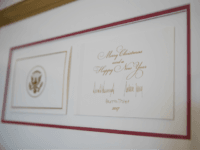 The official White House Christmas card signed by President Donald Trump, first lady Melania Trump, and their son Barron Trump is seen in the East Garden Room during a media preview of the 2017 holiday decorations at the White House in Washington, Monday, Nov. 27, 2017. (AP Photo/Carolyn Kaster)