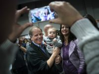 BIRMINGHAM, AL - NOVEMBER 18: Democratic candidate for U.S. Senate Doug Jones poses for a photo with a baby after speaking at a fish fry campaign event at Ensley Park, November 18, 2017 in Birmingham, Alabama. Jones has moved ahead in the polls of his Republican opponent Roy Moore, whose …