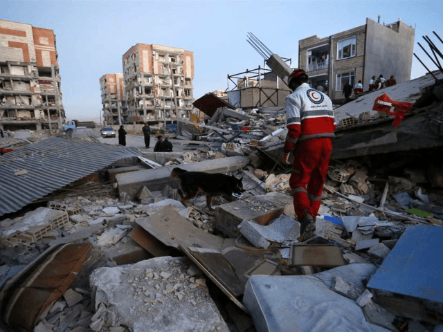 In this photo provided by the Iranian Students News Agency, ISNA, a rescue worker searches debris for survivors with his sniffing dog after an earthquake at the city of Sarpol-e-Zahab in western Iran, Monday, Nov. 13, 2017. A powerful earthquake shook the Iran-Iraq border late Sunday, killing more than two …