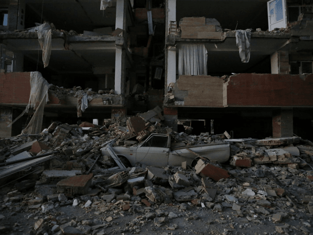 A flattened vehicle underneath building rubble is seen following a 7.3-magnitude earthquake at Sarpol-e Zahab in Iran's Kermanshah province on November 13, 2017. At least 164 people were killed and 1,600 more injured when a 7.3-magnitude earthquake shook the mountainous Iran-Iraq border triggering landslides that were hindering rescue efforts, officials …