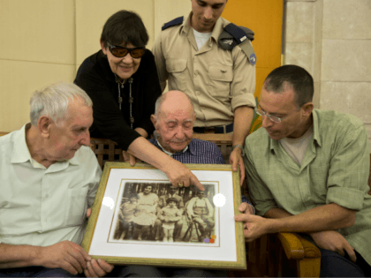In this Thursday, Nov. 16, 2017 photo, Israeli Holocaust survivor Eliahu Pietruszka, center, looks at a picture with Alexandre Pietruszka and family in the central Israeli city of Kfar Saba. Pietruszka who fled Poland at the beginning of World War II and thought his entire family had perished learned that …