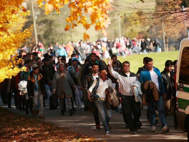 German police lead arriving migrants alongside a street to a transport facility after gathering them at the border to Austria on October 28, 2015 near Wegscheid, Germany. Bavarian Governor Horst Seehofer has accused the Austrian government of wantonly shuttling migrants in buses from the Slovenian border across Austria and dumping them at all hours of day and night at the border to Germany. German authorities have recorded over 7,000 migrants arriving daily since the weekend as a bottleneck of migrants in Slovenia and Croatia finally arrived in Austria. Germany has registered over 800,000 migrants this year and Chancellor Angela Merkel is mounting pressure on European Union member states that so far have shown great reluctance to accept any migrants at all to finally share the burden of accommodating the newcomers, many of whom are refugees fleeing war-torn Syria. (Photo by Johannes Simon/Getty Images)