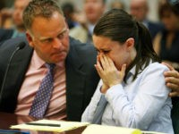 Casey Anthony, right, is comforted by Todd Macaluso, part of her defense legal team, Friday, August 21, 2009, as she cries after seeing her father George Anthony testify during a court hearing, in Orlando, Florida. (Photo by Pool photo by Red Huber/Orlando Sentinel/MCT via Getty Images)