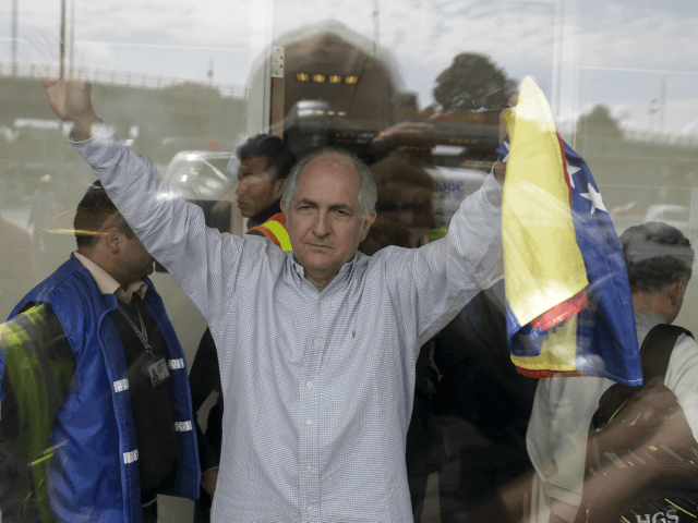 Holding a national Venezuelan flag, ousted Caracas Mayor Antonio Ledezma waves from inside El Dorado international airport, as he prepares for departure, in Bogota, Colombia, Friday, Nov. 17, 2017. Ledezma, one of Venezuela's most prominent opposition leaders, said he plans to take his fight against Venezuela's socialist government to Europe …