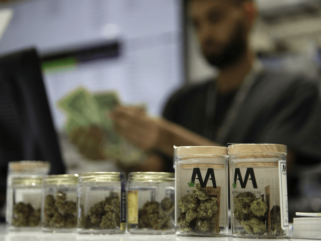 n this July 1, 2017 file photo, a cashier rings up a marijuana sale at the Essence cannabis dispensary in Las Vegas. A medical marijuana patient is asking the Nevada Supreme Court to reconsider its refusal to end mandatory state registration and fees for medical pot cards now that marijuana is legal statewide for recreational use. (AP Photo/John Locher, file)