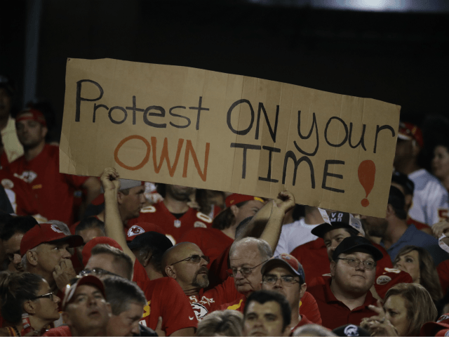 A Kansas City Chiefs fan holds a sign against the anthem protests during the first half of an NFL football game against the Washington Redskins in Kansas City, Mo., Monday, Oct. 2, 2017. (AP Photo/Charlie Riedel)