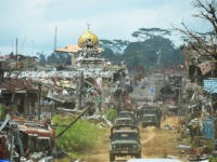 Military trucks drive past destroyed buildings and a mosque in what was the main battle area in Marawi on the southern island of Mindanao on October 25, 2017, days after the military declared the fighting against IS-inspired Muslim militants over. Philippine troops of a southern Philippine city where Islamic State supporters waged a brutal five-month battle began leaving Marawi on October 25, as a group of journalists were given the first ever press tour of the devastated city. / AFP PHOTO / TED ALJIBE (Photo credit should read TED ALJIBE/AFP/Getty Images)