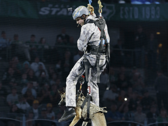 Former Navy Seal Ryan Parrot, top, drops in with a service dog named Patty during a special presentation honoring U.S. armed services veterans between the the first period and second period of an NHL hockey game between the San Jose Sharks and Dallas Stars in Dallas, Monday, March 20, 2017. The Stars won 1-0. (AP Photo/LM Otero)