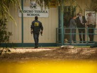 TOPSHOT - FBI agents are seen behind yellow crime scene tape outside Rancho Tehama Elementary School after a shooting in the morning on November 14, 2017, in Rancho Tehama, California Four people were killed and nearly a dozen were wounded, including several children, when a gunman went on a rampage at multiple locations, including a school in rural northern California. / AFP PHOTO / Elijah Nouvelage (Photo credit should read ELIJAH NOUVELAGE/AFP/Getty Images)