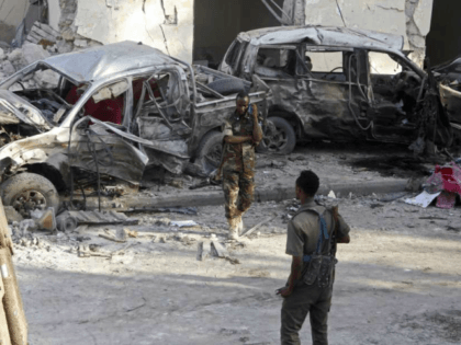 Somali soldiers stand near the wreckage of vehicles in Mogadishu, Somalia, Sunday, Oct 29, 2017, after a car bomb detonated Saturday night. A Somali police officer said security forces ended a night-long siege at a Mogadishu hotel by attackers who stormed the building after a suicide car bomber detonated an …