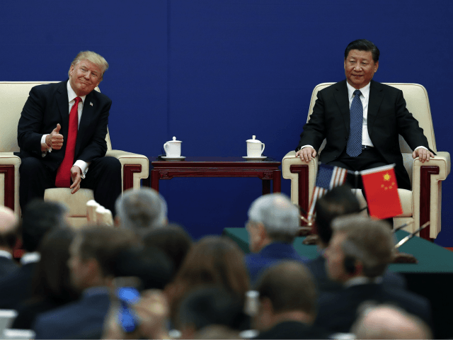 U.S. President Donald Trump gestures to his delegation next to and Chinese President Xi Jinping during a business event at the Great Hall of the People in Beijing, Thursday, Nov. 9, 2017. Trump is on a five-country trip through Asia traveling to Japan, South Korea, China, Vietnam and the Philippines. (AP Photo/Andy Wong)