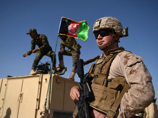 In this photograph taken on August 28, 2017, a US Marine looks on as Afghan National Army soldiers raise the Afghan National flag on an armed vehicle during a training exercise to deal with IEDs (improvised explosive devices) at the Shorab Military Camp in Lashkar Gah in Helmand province. Marines in Afghanistan's Helmand say Donald Trump's decision to keep boots on the ground indefinitely gives them 'all the time in the world' to retake the province, once the symbol of US intervention but now a Taliban stronghold. They may need it. At the hot, dusty Camp Shorab, where many of the recently deployed Marines train their Afghan counterparts in flat, desert terrain, the Afghans admit their army still cannot fight alone. / AFP PHOTO / WAKIL KOHSAR (Photo credit should read WAKIL KOHSAR/AFP/Getty Images)