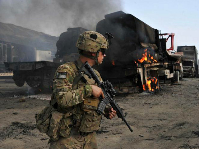 A US soldier investigates the scene of a suicide attack at the Afghan-Pakistan border crossing in Torkham, Nangarhar province on June 19, 2014. Three Taliban suicide attackers set ablaze 37 NATO military vehicles in Afghanistan on June 19, local officials said, though the coalition confirmed only that several vehicles were damaged. AFP PHOTO/Noorullah Shirzada (Photo credit should read Noorullah Shirzada/AFP/Getty Images)
