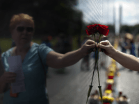 Carol Bates, of California, holds a rose against the Vietnam Veterans Memorial in Washington, Sunday, June 18, 2017, during the Vietnam Veterans Memorial Fund's annual Father's Day Rose Remembrance in honor of Father's Day. (AP Photo/Carolyn Kaster)