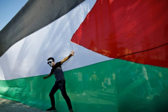 A Palestinian youth celebrates in front of his national flag in Gaza City on October 12, 2017 after rival factions Hamas and Fatah reached an agreement on ending a decade-long split