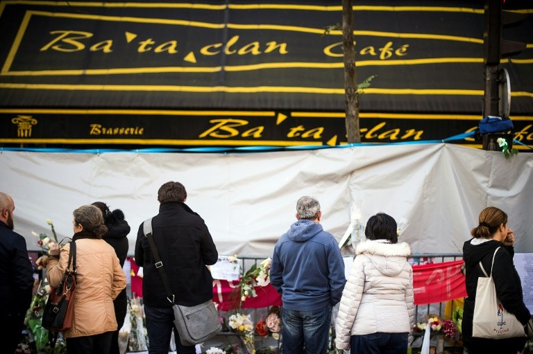 People pay tribute in front of the Bataclan after the November 13, 2015 attack