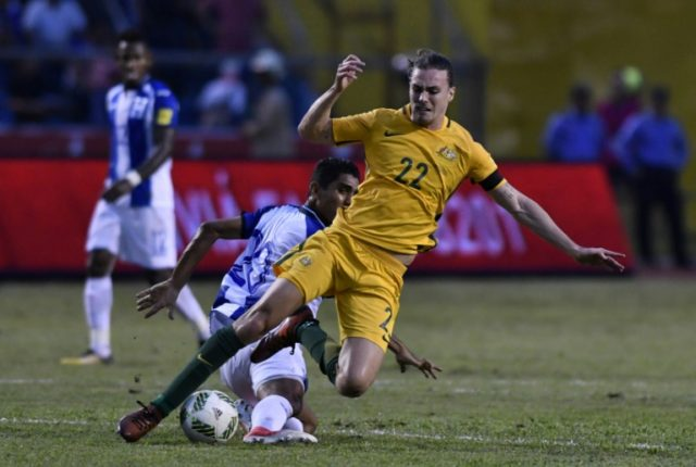 Honduras' Jorge Claros (L) and Australia's Jackson Irvine fall during the first leg football match of their 2018 World Cup qualifying play-off in San Pedro Sula, Honduras, on November 10, 2017