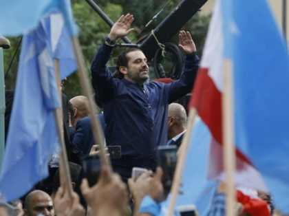 Lebanese Prime Minister Saad Hariri greets cheering supporters outside his home in Beirut on November 22, 2017 after announcing he had agreed to put his shock resignation on hold