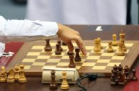 Norway's Magnus Carlsen (L) moves his rook during his game against Cuba's Leinier Dominguez during the Men's Blitz tournament part of the FIDE World Chess Rapid & Blitz Championships 2016, in Doha December 29, 2016