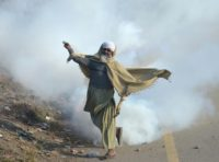 A Pakistani protester of the Tehreek-i-Labaik Yah Rasool Allah Pakistan religious group throws a tear gas shell back towards police during a clash in Islamabad on November 25