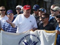 President Donald Trump speaks with members of the Coast Guard who he invited to play golf at Trump International Golf Club, Friday, Dec. 29, 2017, in West Palm Beach, Fla. (AP Photo/Evan Vucci)