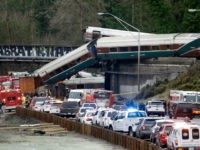 Cars from an Amtrak train lay spilled onto Interstate 5 below as some remain on the tracks above Monday, Dec. 18, 2017, in DuPont, Wash. The Amtrak train making the first-ever run along a faster new route hurtled off the overpass Monday near Tacoma and spilled some of its cars …
