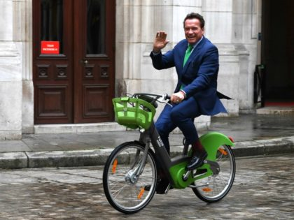 Former Governor of the US State of California Arnold Schwarzenegger waves as he rides a bicycle in Paris on December 11, 2017, on the sidelines of meetings with Mayor of Paris Anne Hidalgo. / AFP PHOTO / ALAIN JOCARD (Photo credit should read ALAIN JOCARD/AFP/Getty Images)