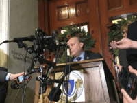 Massachusetts Senate President Stan Rosenberg speaks from behind a podium outside his office at the Statehouse to a throng of media Friday, Dec. 1, 2017, in Boston. Rosenberg said his husband, Bryon Hefner, will soon be entering treatment for alcoholism, one day after The Boston Globe reported that several men had accused Hefner of sexual assault and harassment. Some of the men had professional dealings with the Legislature. (AP Photo/Bob Salsberg)