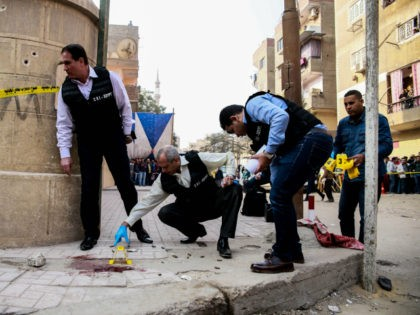 Egyptian security members and forensic police inspect the site of a gun attack outside a church south of the capital Cairo, on December 29, 2017. A gunman opened fire on a church, killing at least nine people before policemen shot him dead, state media and officials said. / AFP PHOTO …