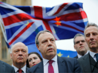 Democratic Unionist Party (DUP) Deputy Leader Nigel Dodds (C) speaks to journalists outside the Houses of Parliament in central London on December 5, 2017, as demonstrators wave Union and European Union (EU) flags behind. British Prime Minister Theresa May scrambled Tuesday to salvage a deal over the post-Brexit border in …